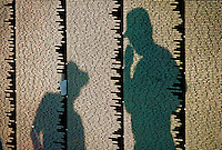 Men's shadows on Vietnam War Memorial Wall