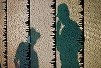 Men's shadows on Vietnam War Memorial Wall