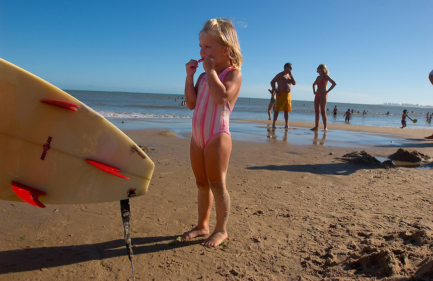 Victoria Mendizabal, 4, of Argentina, savors a popsicle on a beach in La Barra near Punta del Este, Uruguay. The venerable South American beach resort is having a rennaisance. (Kevin Moloney for the New York Times)