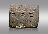 Picture & image of Hittite monumental relief sculpted orthostat stone panel of a Procession. Basalt, Karkamıs, (Kargamıs), Carchemish (Karkemish), 900-700 B.C.  Marching female figures. Anatolian Civilisations Museum, Ankara, Turkey.<br /> <br /> It is a depiction of three marching female figures in long dress with a high headdress at their head. These women are considered to be the nuns of the Goddess Kubaba. They have a bunch of Spica in their right hand, and objects similar to a sceptre in their left hand.<br /> <br /> Against a gray background.