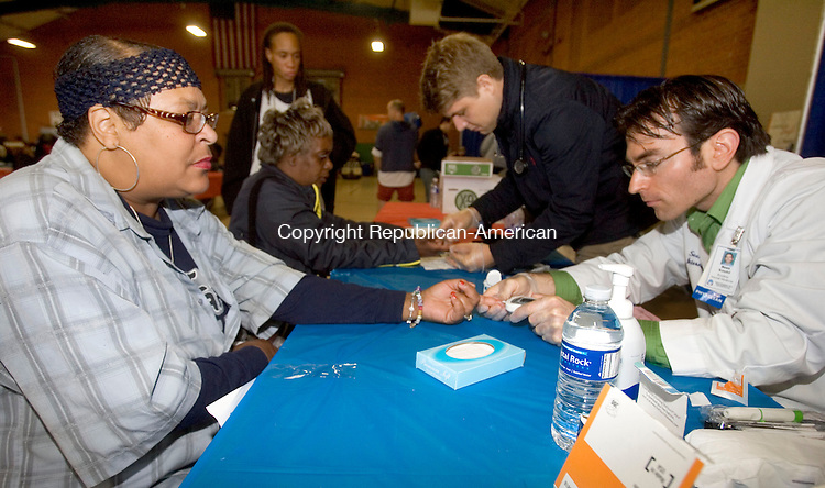 WATERBURY CT. 17 October 2014-101714SV04-From left, Robin Sparkman of Waterbury has her blood sugar checked by Sean Kandel of Waterbury Hospital during the United Way of Greater Waterbury's Project Homeless Connect event at the Armory in Waterbury Friday.<br /> Steven Valenti Republican-American