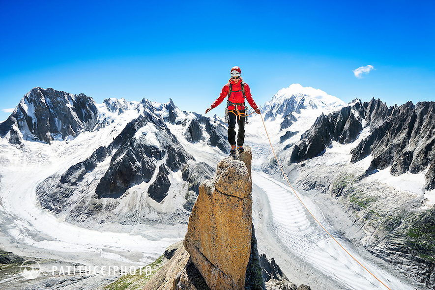 Climbing the Aiguille du Moine's South Ridge Integral, D. A long alpine rock ridge in Chamonix, France. The climber is balancing on a thin block of rock near the top of the peak.