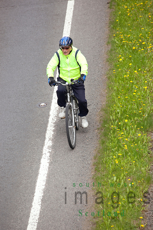 Looking down on cyclist old man cycling exercise along the edge of a main road A75 beside grass verge Scotland UK