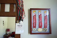 STAFF PHOTO SAMANTHA BAKER &bull; @NWASAMANTHA<br /> Medals from the 2010 USA Games are kept in a glass case and hung on the wall Friday, May 2, 2014, in Sowers' bedroom. &quot;Canyon is probably the best swimmer in the state,&quot; said David Thrift, Sower's sprint triathlon partner.
