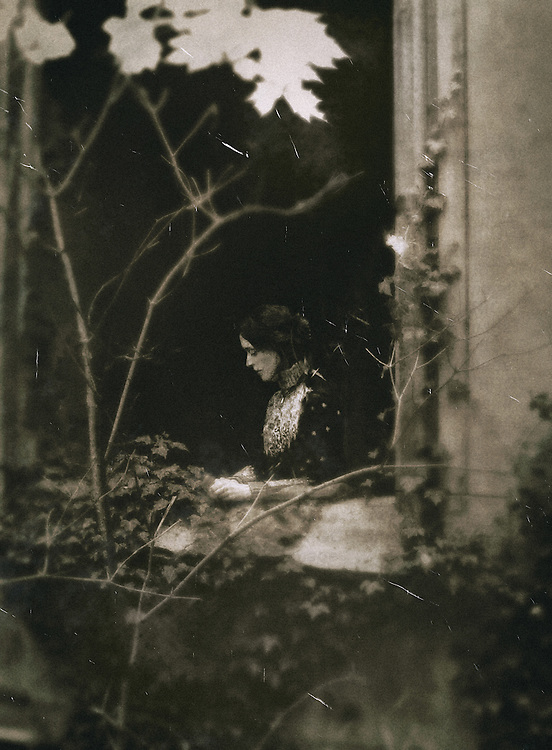 A woman in a victorian outfit and dark hair, standing at the window of an old building hidden behind the trees.