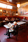 USA, California, San Francisco, a man ready the newspaper at at table inside Cafe Trieste, North Beach