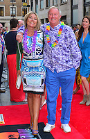 Jane Bird &amp; Chris Tarrant<br /> The &quot;Bula Quo!&quot; UK film premiere, Odeon West End cinema, Leicester Square, London, England.<br /> July 1st, 2013<br /> full length blue purple print pattern dress lei flowers arm over shoulder trousers shirt hand in pocket couple <br /> CAP/BF<br /> &copy;Bob Fidgeon/Capital Pictures
