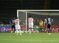 BOGOTA - COLOMBIA -21 -02-2015: Fernando Uribe (Izq.) jugador de Millonarios anota gol a Pablo Mina (Cent.) portero de Cortulua, durante partido entre Millonarios y Cortulua por la fecha 5 de la Liga Aguila I-2015, jugado en el estadio Nemesio Camacho El Campin de la ciudad de Bogota. / Fernando Uribe, (L) player of Millonarios scored a gaol to Pablo Mina (C), goalkeeper of Cortulua, during a match between Millonarios and Cortulua, for the date 5 of the Liga Aguila I-2015 at the Nemesio Camacho El Campin Stadium in Bogota city, Photo: VizzorImage / Luis Ramirez / Staff.