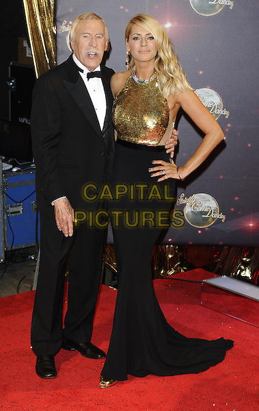 Bruce Forsyth &amp; Tess Daly<br /> The red carpet launch for 'Strictly Come Dancing' at Elstree Studios, Borehamwood, England.<br /> September 3rd, 2013<br /> full length gold sleeveless sequins sequined black skirt top dress hand on hip tuxedo  <br /> CAP/FIN<br /> &copy;Steve Finn/Capital Pictures
