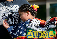 NWA Democrat-Gazette/CHARLIE KAIJO Khloe Pascual, 7, of Springdale plays with a tag around her mother's neck that says &quot;Families belong together&quot; while she speaks during a rally, Saturday, June 30, 2018 at the downtown square in Fayetteville. <br /> <br /> The rally in Fayetteville is one of hundreds of rallies planned as part of a Families Belong Together national day of action to protest the administration&rsquo;s &ldquo;zero tolerance&rdquo; immigration policy, which remains in effect. Advocacy groups such as MoveOn, the Human Rights Campaign and the American Civil Liberties Union have joined in, and at least 130 rallies in 48 states are planned.