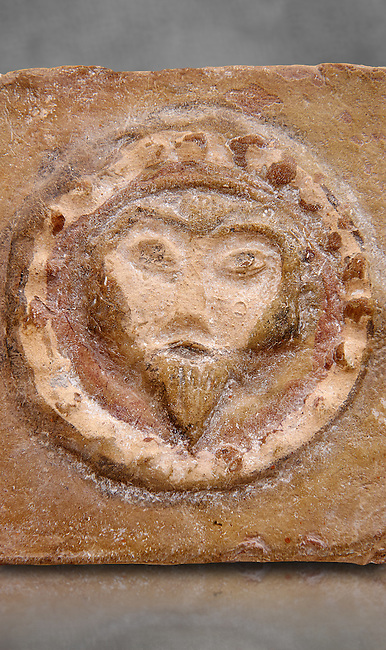 Detail of a 6th-7th Century Eastern Roman Byzantine  Christian Terracotta tiles depicting Christ - Produced in Byzacena -  present day Tunisia. <br /> <br /> These early Christian terracotta tiles were mass produced thanks to moulds. Their quadrangular, square or rectangular shape as well as the standardised sizes in use in the different regions were determined by their architectonic function and were designed to facilitate their assembly according to various combinations to decorate large flat surfaces of walls or ceilings. <br /> <br /> Byzacena stood out for its use of biblical and hagiographic themes and a richer variety of animals, birds and roses. Some deer and lions were obviously inspired from Zeugitana prototypes attesting to the pre-existence of this province's production with respect to that of Byzacena. The rules governing this art are similar to those that applied to late Roman and Christian art with, in the case of Byzacena, an obvious popular connotation. Its distinguishing features are flatness, a predilection for symmetrical compositions, frontal and lateral representations, the absence of tridimensional attitudes and the naivety of some details (large eyes, pointed chins). Mass production enabled this type of decoration to be widely used at little cost and it played a role as ideograms and for teaching catechism through pictures. Painting, now often faded, enhanced motifs in relief or enriched them with additional details to break their repetitive monotony.<br /> <br /> The Bardo National Museum Tunis, Tunisia. Against a grey art background.