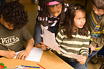 Public elementary school Grade 2 group working on math activity girl consulting classmates