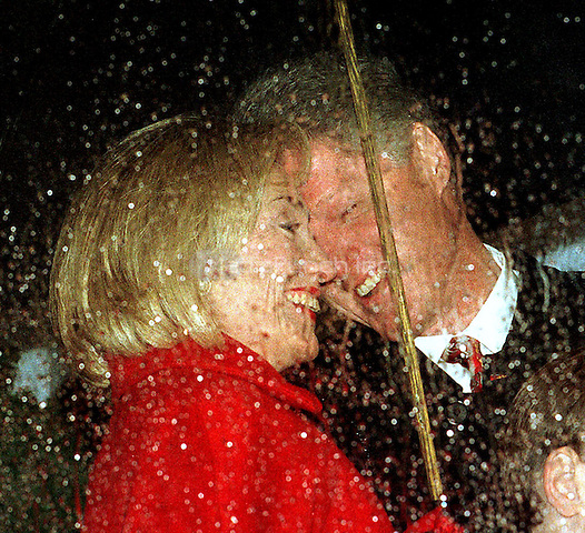 United States President Bill Clinton and first lady Hillary Rodham Clinton seem sharing a happy Christmas memory as rain falls during the National Christmas Tree lighting ceremony on the Ellipse in Washington, DC on December 4, 1997.<br /> Credit: Ron Sachs / CNP/MediaPunch