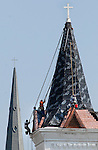 Steeplejacks with Inspired Heights work on covering the steeple of the First Methodist Church in downtown Huntsville with copper.  Times photographer Bob Gathany  (in orange shirt & hat) taking photos of steeplejacks 110 feet above the ground.