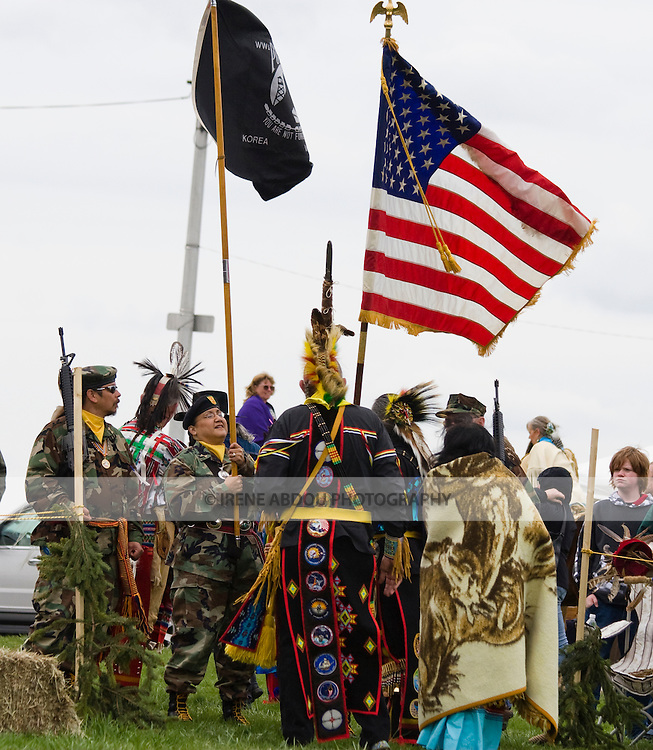 "Native Americans at the Healing Horse Spirit PowWow in Mt. Airy, Maryland carry an American flag POW-MIA flag.  They standy ready for the ""Grand Entrance.""  Many Native Americans are U.S. soldiers or veterans.  One man in traditional regalia sports US military badges sewn down the length of his regalia in a vertical stripe."