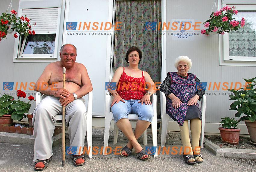 I FRATELLI MINICHELLI, SERGIO (A SINISTRA) E MARIA ANTONIA (A DESTRA) CON SUA FIGLIA ALL'ESTERNO DEL LORO CONTAINER. <br /> Giove di Valtopina 14/06/2010 Giove fu colpito dal terremoto che ha coinvolto le regioni di Marche e Umbria nel settembre 1997. Dopo 13 anni ancora 5 o 6 famiglie, per lo pi&ugrave; composte da persone anziane, alcune completamente sole, vivono in container messi a disposizione dalla Protezione Civile. Il caso Giove nasce dalla scelta da parte del consorzio per la ricostruzione, di una societ&agrave; appaltatrice che gi&agrave; nel 1998 stava fallendo, la SEM di Perigia. Questa societ&agrave;, come affermano gli abitanti, ha lavorato malissimo nel cantiere, demolendo abitazioni senza ordinanza di demolizione, ed eseguendo finti consolidamenti, senza rispettare le norme vigenti in materia.<br /> Inoltre la SEM, oltre ad aver percepito prima di fallire una somma pari al 40% dei fondi per la ricostruzione, percepisce circa 300.000 euro per lo smaltimento delle macerie, contenenti, oltre a materiali da costruzione, amianto ed eternit, sostanze pericolose per la salute, che avrebbe dovuto smaltire in una discarica autorizzata. Queste macerie  in realt&agrave; vengono &quot;buttate&quot; in un campo adiacente il paese, dove ancora si possono vedere seppur ricoperte ormai da erbacce che quasi le nascondono alla vista. <br /> Mentre la SEM dichiara fallimento, gli abitanti del paese fanno partire degli esposti alla Guardia di Finanza di Foligno, all&rsquo;Ispettorato del Lavoro e alla A.S.L.<br /> Il lodo arbitrale d&agrave; ragione agli sfollati che avevano inoltrato denuncia ravvisando gravi inadempienze da parte della ditta e attestando la ''pedestre qualit&agrave; dei lavori'. Tutto per&ograve; viene rimesso al giudice fallimentare, e c'&egrave; ancora un giudizio in atto.<br /> Viene indetta una gara d&rsquo;appalto alla quale partecipano due ditte, la Bordicchia di Nocera Umbra e la Novatecno di Perugia. La prima fa un offerta pi&ugrave; alta del