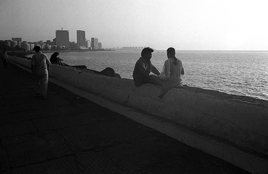 A couple chat sitting on the see wall watching the sunset near Chowpatty Beach, Mumbai India.  January 2000