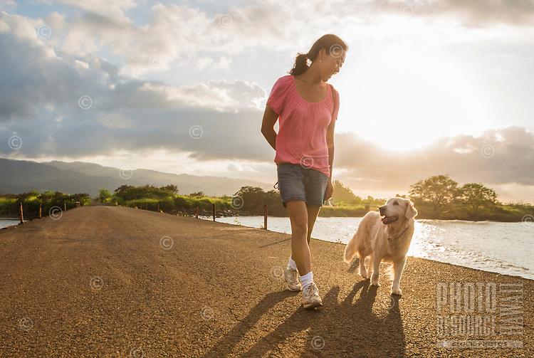 Woman walking with dog on bridge at sunset, North Shore, O'ahu