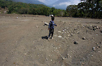 Diego Elias Mendoza Santos, 12, also known as Rambo, looks for the spot of his former home in an area of Panabaj, Guatemala on Tuesday, March 20, 2007. A deadly mudslide here was spawned by rains associated with Hurricane Stan in October 2005. Initially, up to 500 Tzujutil Maya villagers were believed to have been killed by the mudslide, which essentially  wiped away the town. Rambo lost his parents and a sister and brother. Forensic anthropologists from the Fundación de Antropología Forense de Guatemala have been working to unearth the bodies of the missing and have recovered more than 100. They have also found the number of missing to be lower than originally thought, after many people were located in shelters or living in other towns after the disaster.