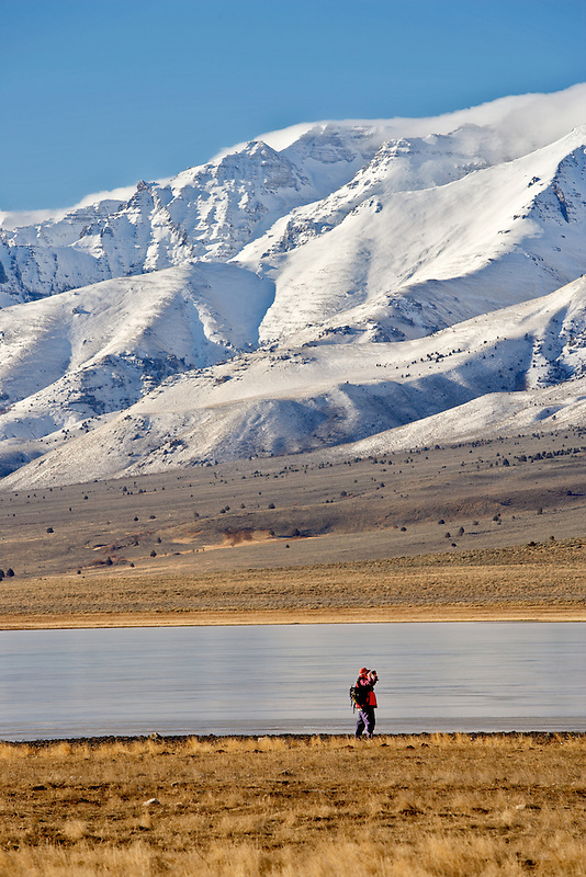 Photographer on frozen Mann Lake with Steens Mountain. Oregon