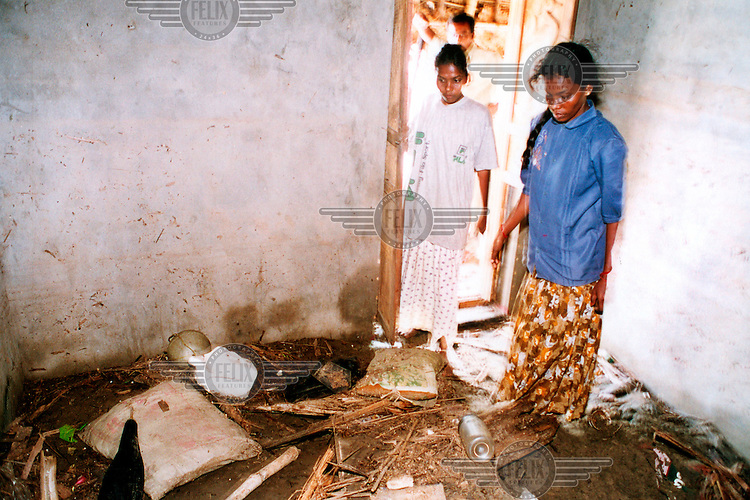 A family return to their flooded home following the tsunami which struck South Asia on 26/12/2004..An underwater earthquake measuring 9 on the Richter scale triggered a series of tidal waves which caused devastation when they struck dry land. 12 countries were affected by the tsunami, with a combined death toll of over 150,000.