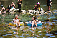 Best friends in bikini enjoying time together outdoors at top Austin tourist attraction, Barton Springs Spillway in Austin, Texas - Concept of freedom and happiness with two girlfriends having fun in the summer time.