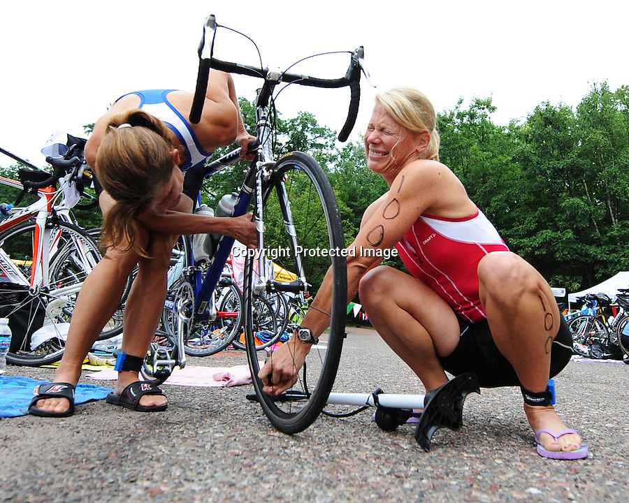 A triathlon competitor attempts to fix her biker prior to the event's start.