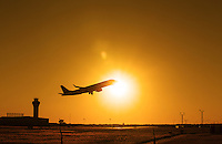 Jet Airplane taking off at sunset from the Austin ABIA Airport. Image contains lens flare with copy space.