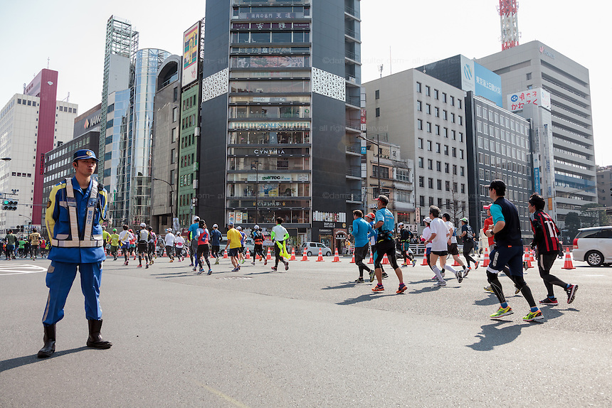 A police stands guard on a street in Ginza as runners pass by during the 10th Tokyo Marathon took place on a fine spring day in Tokyo Japan. Sunday February 28th 2016. Thirty-six thousand runners took part with Ethiopian,  Feyisa Lilesa winning the  men's competition and  Kenyan, Helah Kiprop victorious in the women's race.