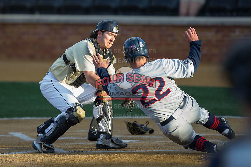 Wake Forest Demon Deacons catcher Ben Breazeale (9) puts the tag on Joe Deroche-Duffin (22) of the UConn Huskies as he tries to score a run at Wake Forest Baseball Park on March 17, 2015 in Winston-Salem, North Carolina.  The Demon Deacons defeated the Huskies 6-2.  (Brian Westerholt/Four Seam Images)