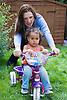 Toddler playing on a bike in the garden with her mother,