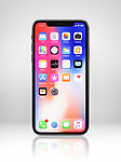 Apple iPhone X, large screen smartphone, with colorful desktop on its display. The phone is isolated on light gray studio background with a clipping path.