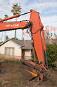 A large excavator in front of a house ready for demolition. This one-story house on a 10,000 square foot lot will be replaced with a 4,060 square foot two story single family home with an in-law unit. Cupertino, California, USA