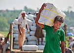 Rohingya refugees unload a truck carrying tarps, blankets and other items in the Jamtoli Refugee Camp near Cox's Bazar, Bangladesh. The relief items were provided by Christian Aid, a member of the ACT Alliance.<br /> <br /> More than 600,000 Rohingya have fled government-sanctioned violence in Myanmar for safety in Bangladesh.