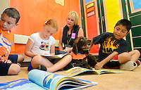 From left, John DiGiovanni, Amelia Trabachino, and Jeff Romero, all 8 years old, reads to Roxy the Reading Dog as Roxy's owner Diane Smith sits in the background at Gayman Elementary School Friday June 12, 2015 in Doylestown, Pennsylvania.  (Photo by William Thomas Cain/Cain Images)