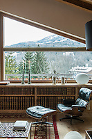 An Eames lounge chair and ottoman in front of the living room window of this contemporary chalet