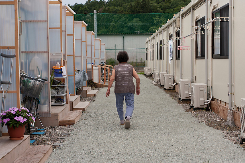 An older returns to her temporary housing in Watari, Sendai, Miyagi. Sunday July 3rd 2011. All 90 houses are being used by survivors of the earthqauke and tsunami from the town of Arahama. Most moved there on May 22nd after having spent time in evacuation centres. They expect to be in this temporary housing for around two years.