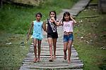 Three indigenous girls walk along a wooden sidewalk in Atalaia do Norte in Brazil's Amazon region.