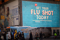 An illuminated sign on the Walgreen's drugstore in Times Square in New York advertises that flu shots are available, seen on Friday, January 24, 2014.  (© Richard B. Levine)