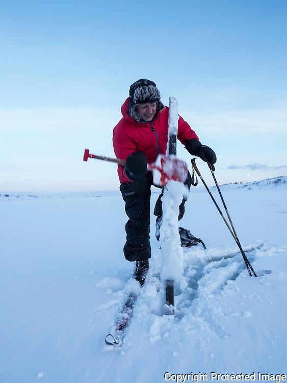 Mann med store kladder under skiene. Dårlig føre, klabbeføre. ---- Man with snow under skis.