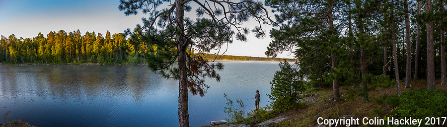 BWCA, MN, 7/31/17- Morning sun lights the pines of Sunday Bay as a fisherman works the shoreline of the Boundary Water Canoe Area's Crooked Lake. <br /> <br /> EDITOR'S NOTE: This image is comprised of multiple photos taken at the same moment and stitched together in photoshop to create a panorama.<br /> <br /> <br /> COLIN HACKLEY PHOTO