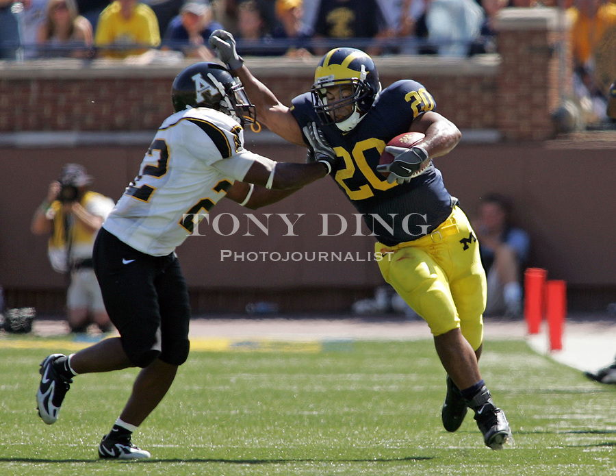 1 September 2007: Michigan running back Mike Hart (20) is pushed towards the sideline by Appalachian State defensive back Leonard Love (22) in the 2007 season opener college football game between the Michigan Wolverines and Appalachian State Mountaineers at Michigan Stadium in Ann Arbor, MI. No. 5 ranked Michigan was upset 32-34.