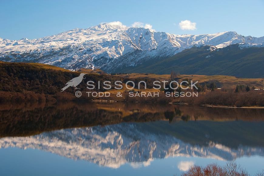 Snow covered Coronet eak is reflected in Lake Hayes, Queenstown, Southern Lakes