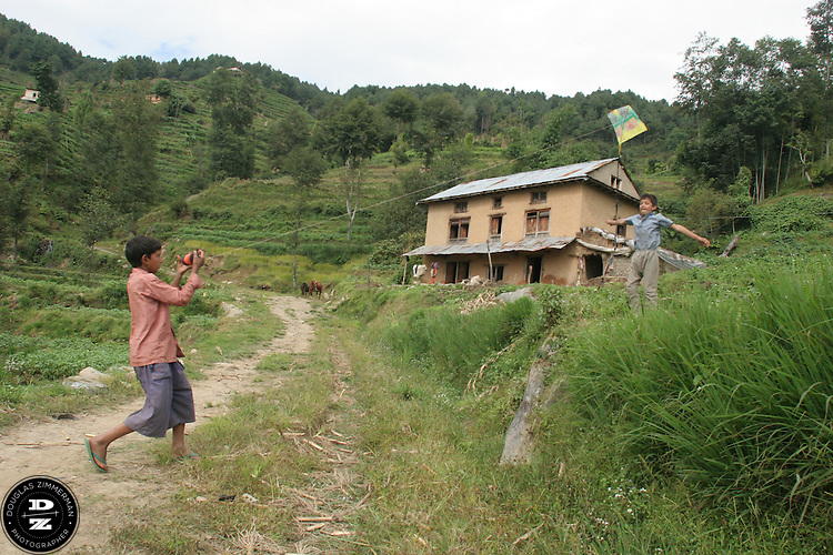 Two village children play with a kite in the  village of Tukucha, Nepal.  Photograph by Douglas ZImmerman