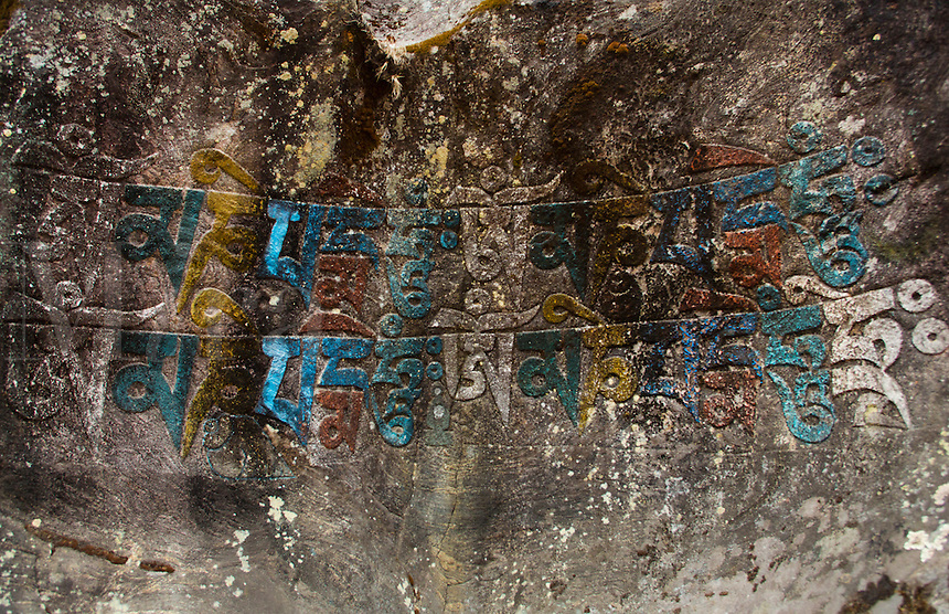 Nepal Himalayas mantra carved into the rockface and painted, outside the village of Bengkar, Solukhumbu remote Mt Everest