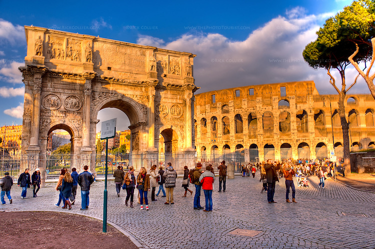 The Colosseum and nearby Constantine's Arch seem to glow gold in the last rays of the setting sun.