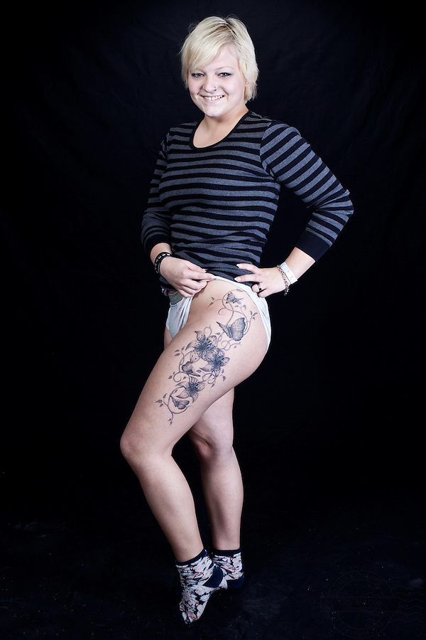 Young danish woman with floral tattoo with butterflies on upper thigh. Also the initials MM on upper right arm.<br />