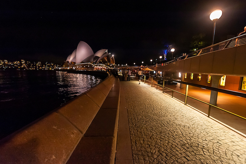 People enjoying the view of Sydney harbor from the Opera Bar (Sydney Opera House in background) at night, Sydney, New South Wales, Australia