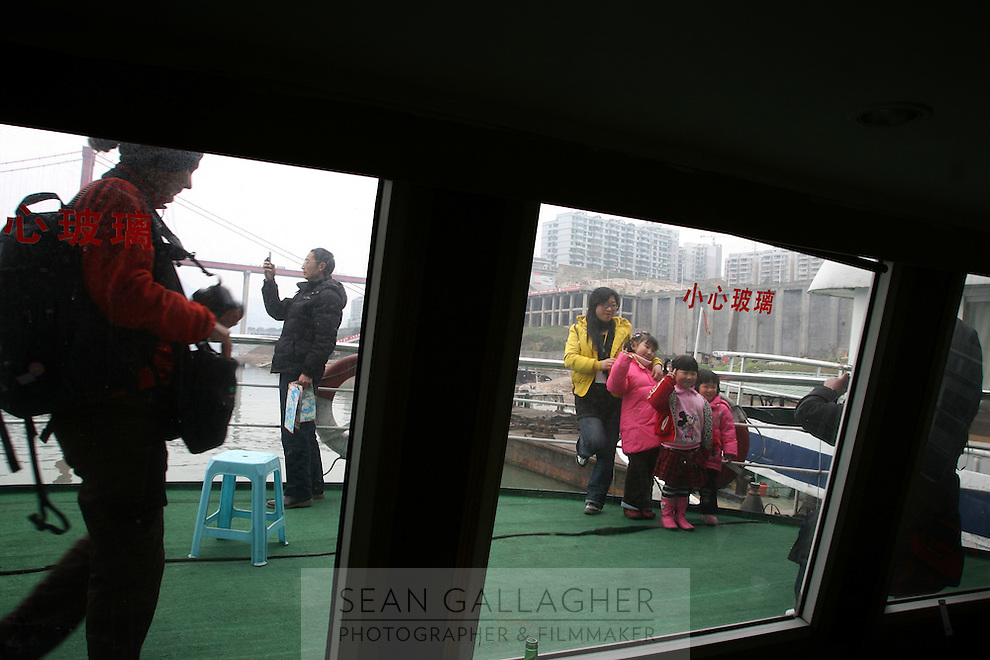 CHINA. Chongqing Province.  Passengers on a boat on the Yangtze River near the three Gorges. The flooding of the three Gorges, by damming the Yangtze near the town of YiChang, has remained a controversial subject due to the negative environmental consequences and the displacement of millions of people in the flood plain. The Yangtze River however is reported to be at its lowest level in 150 years as a result of a country-wide drought. It is China's longest river and the third longest in the world. Originating in Tibet, the river flows for 3,964 miles (6,380km) through central China into the East China Sea at Shanghai.  2008.