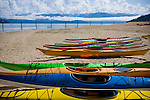Idaho, Sandpoint. Colorful kayaks on the sandy shore of Lake Pend Oreille with Cabinet mountains still covered in snow in Spring.